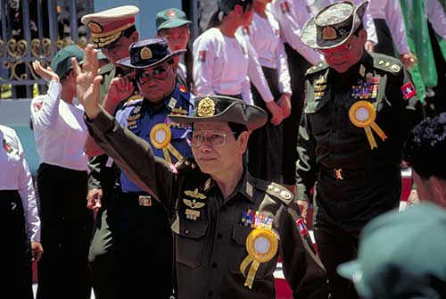 Unreal Politick: Khin Nyunt (center) and other Burmese generals pressing the cowered flesh in Tachilek in 1996. Once head of Burma's notorious Military Intelligence (MI), Khin Nyunt is today (2004) considered a moderate in the ruling junta.