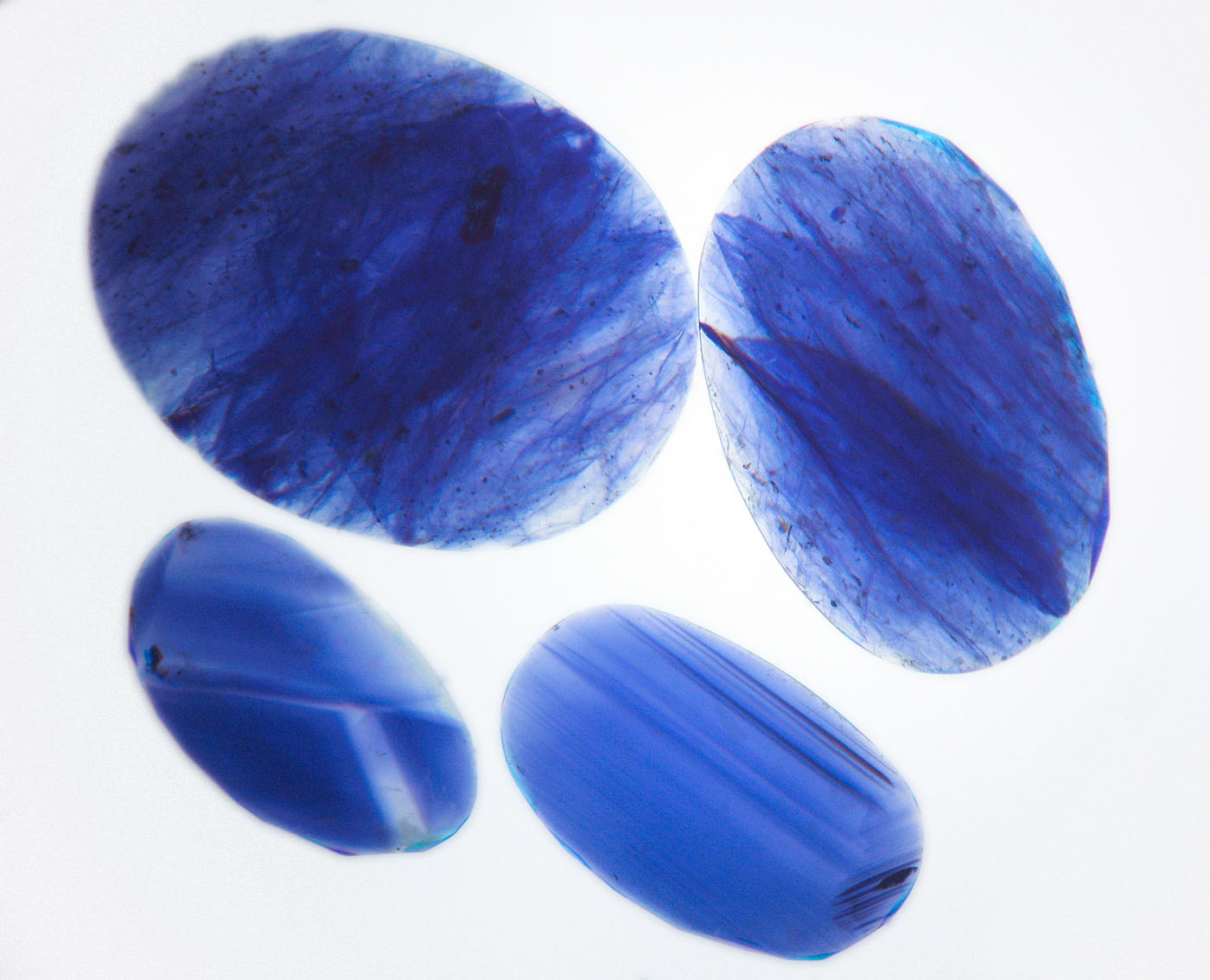 Figure 12. Immersion in di-iodomethane (methylene iodide) in diffuse light-field illumination quickly reveals the blue color concentrations in the cobalt-glass filled sapphires (top two stones), whereas natural sapphires show angular color zoning (lower two stones). Image corrected to remove yellow color of liquid. (Photo: Wimon Manorotkul, Lotus Gemology).