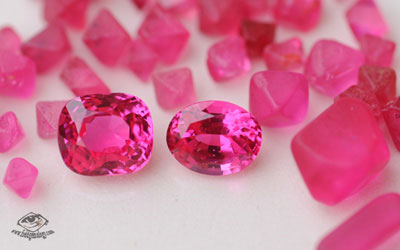 Hot pink spinels in rough and cut form from Namya, Burma.