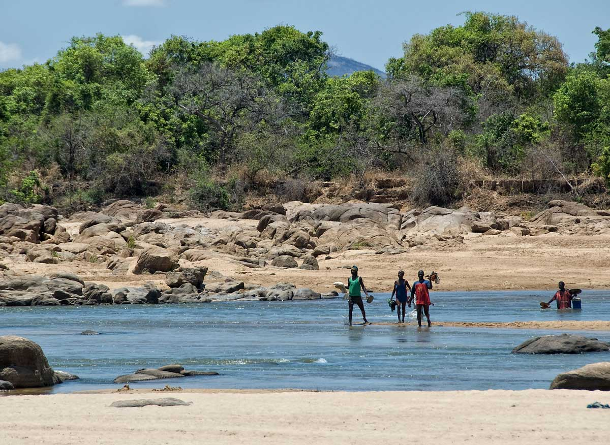 Miners fording the Ruvuma river that separates Tanzania from Mozambique, in Tanzania's Tunduru district. Gems are found on both sides of the river. Lotus Gemology.