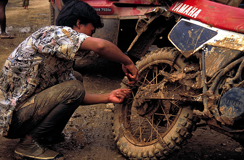 At Nyaungbin, a motorcyclist is seen removing chains. He told the authors it took him ten hours to ride from Hpakan, and he only fell five times.