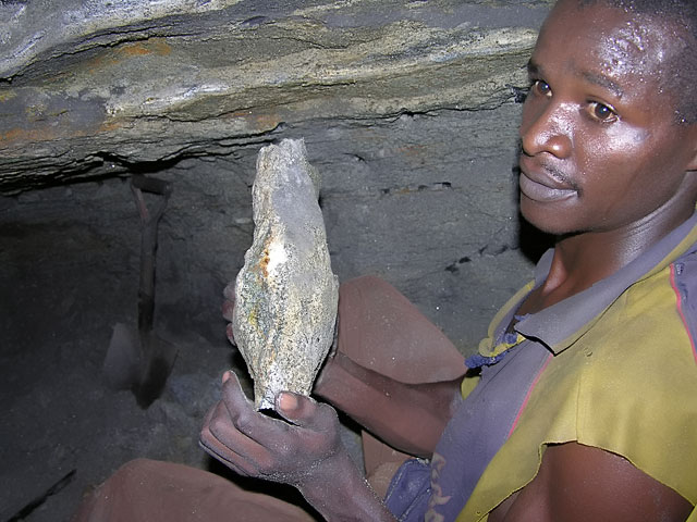 A young Kenyan miner collecting a tsavorite porphyroblast about 20 meters underground in the Tsavo area. Photo: J.B. Senoble, 2005.